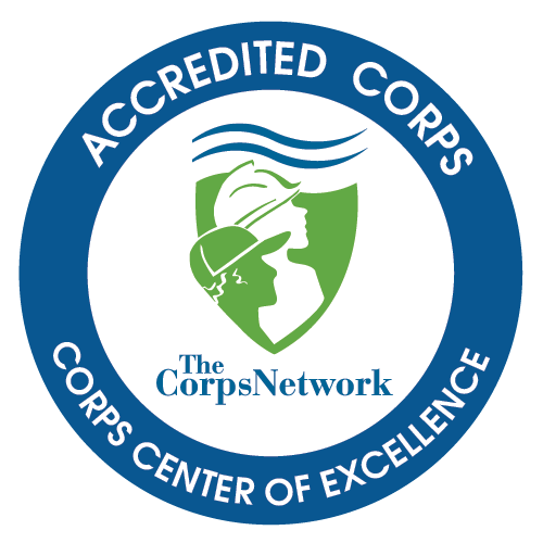 The Corps Network logo. Reads: The Corps Network in middle, depicting two Corpsmembers in a green shield starring off in the distance. Outside circle reads: Accredited Corps, Corps Center of Excellence.