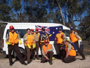 CCC Corpsmembers pose in front of Australian flag and vehicle