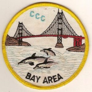 Photo of uniform patch, reads CCC Bay Area, depicts dolphins swimming under Bay Bridge