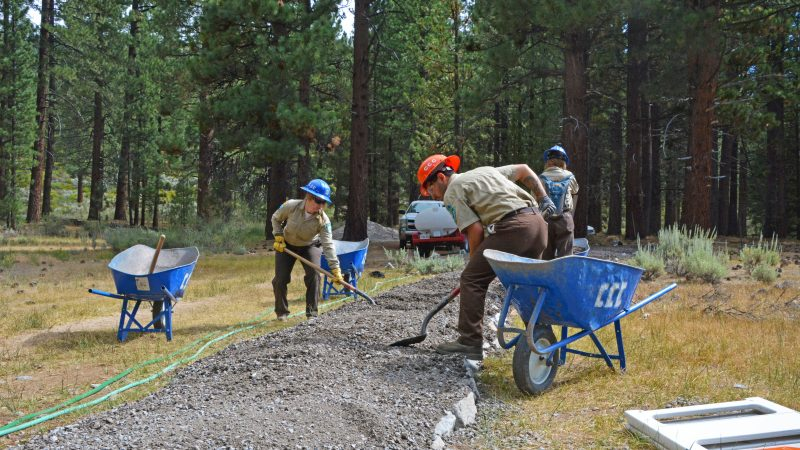 Male Corpsmember in foreground and female Corpsmember in background shovel gravel to build a trail in wilderness