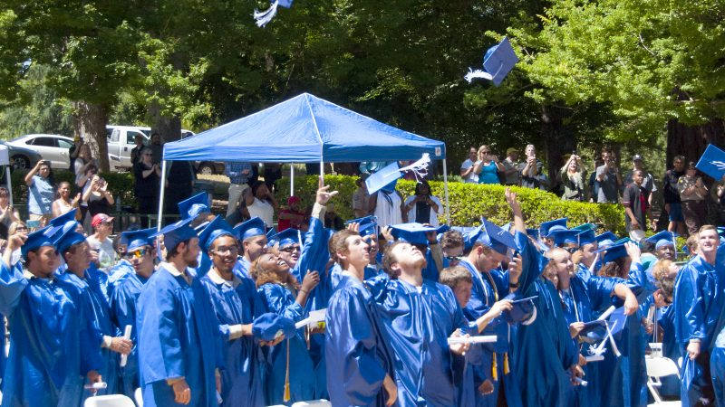 A large group of graduates in blue robes toss their caps into the air.