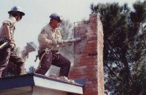 Corpsmembers use pneumatic equipment to tear down damaged chimney of home in Santa Clarita area