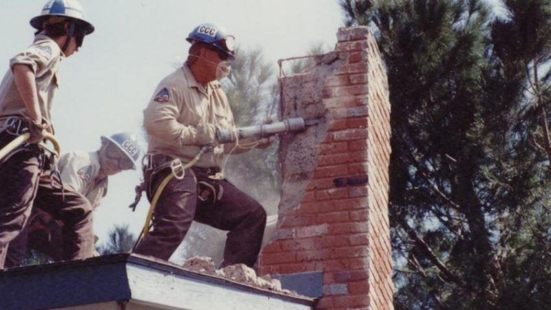 Corpsmembers use pneumatic tool to remove bricks from damaged chimney