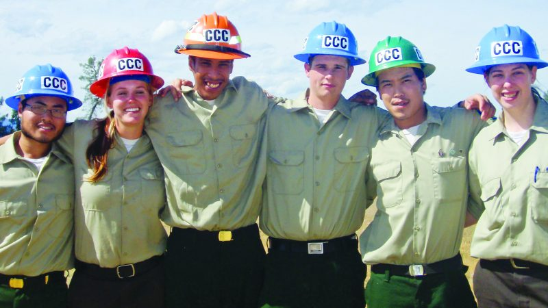 Corpsmembers wearing different color helmets link arms and pose for a photo