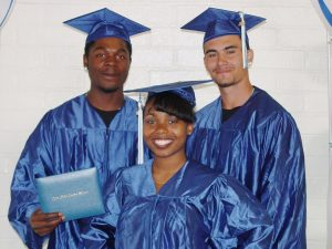 Three Corpsmembers pose with high school diplomas in cap and gowns