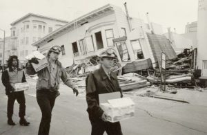 Three CCC Corpsmembers carry supplies in front of leveled building on San Francisco street 1989