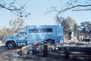 Blue CCC crew vehicle parked in fire ravaged neighborhood