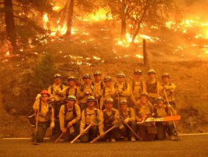 Fire crew Corpsmembers pose in equipment while hillside behind them is engulfed in flames