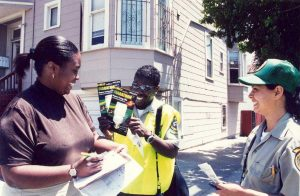 Corpsmembers handing out brochures on city street