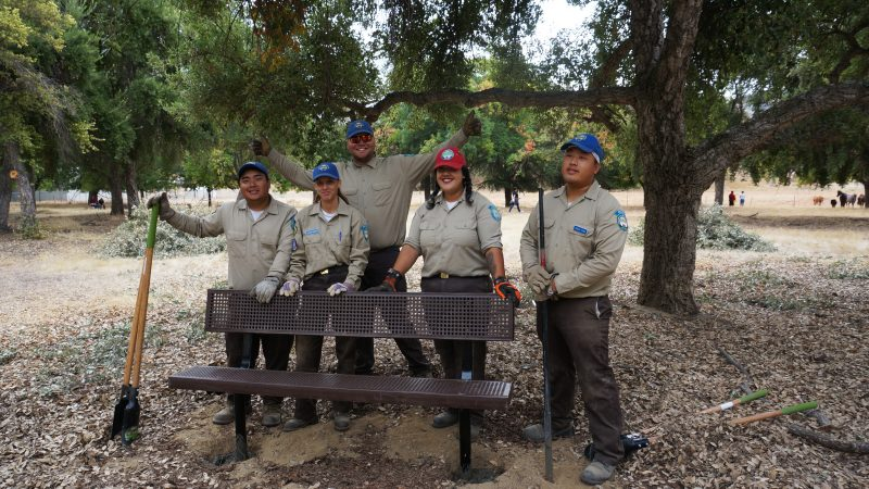 Fresno Corpsmembers stand at metal bench they installed in park