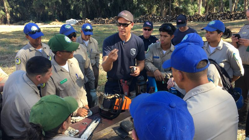 A group of Corpsmembers circle around a CAL Fire instructor, as a disassembled chainsaw lies on the table in the middle of the group.