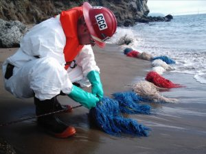 Corpsmember ties knot in tyvek suit assisting in oil spill recovery along beach