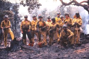 Corpsmembers in full wildland fire equipment post for photo
