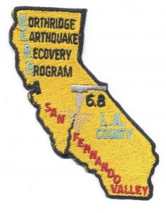 Photo of uniform patch. Shape of California, reads Northridge Earthquake Recovery Program, San Fernando Valley, 6.8, L.A. County