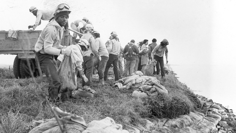 Vintage photograph of corpsmembers working with sandbags.