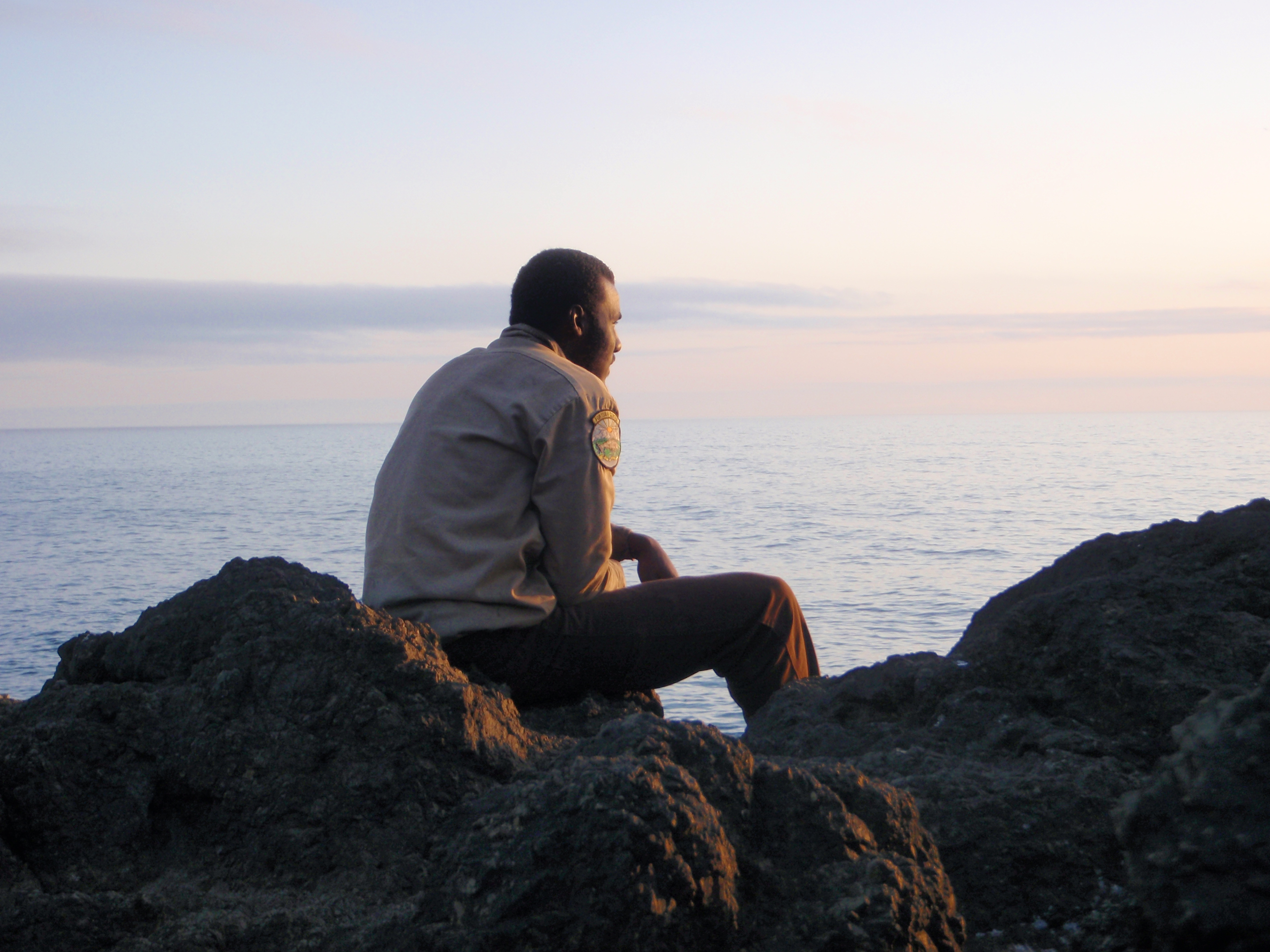 Corpsmember sitting on a rock looking at the sunset.