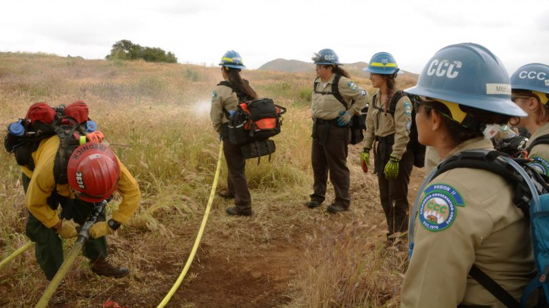 A Corpsmember sprays water over a field while holding a firehose. More Corpsmembers watch.