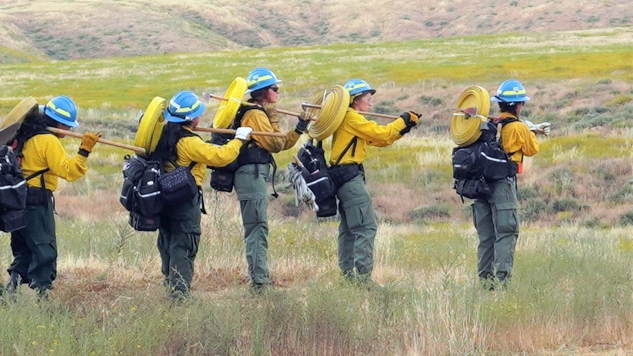 Corpsmembers from the Inland 5 all-female BLM fire crew prepare to lay hose.