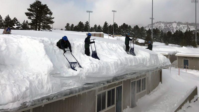 Corpsmembers use snow shovels atop a school roof to remove four feet of standing snow