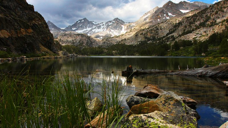 Photo of backcountry lake, water in the foreground, mountains in the deep background