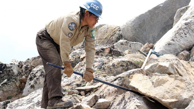 Female Corpsmember wearing PPE uses rock bar to lift giant rock during trail work in backcountry