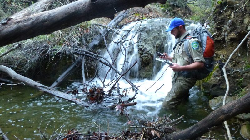 Corpsmember Dustin Casey stands knee deep in the water of the redd, wearing a blue cap and hiking backpack as he consults an electronic handheld device and prepares to write data on a notepad in his other hand.