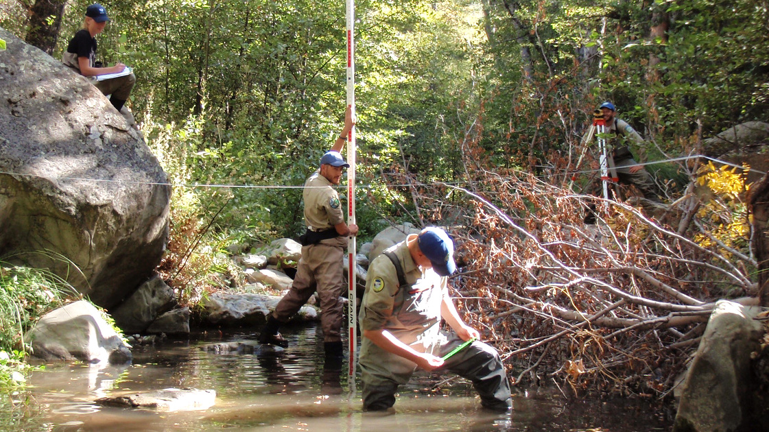 Two Corpsmembers in hip-waders stand in creek taking measurements, while others in background record data