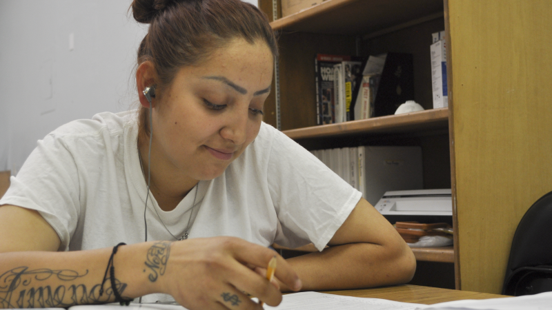 A female Corpsmember sits at a table doing homework while listening to her earphones.