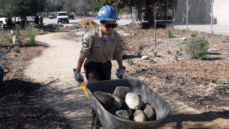 Image. Female Corpsmember in blue helmet, safety glasses, and gloves pushes wheelbarrow full of rocks along park trail.