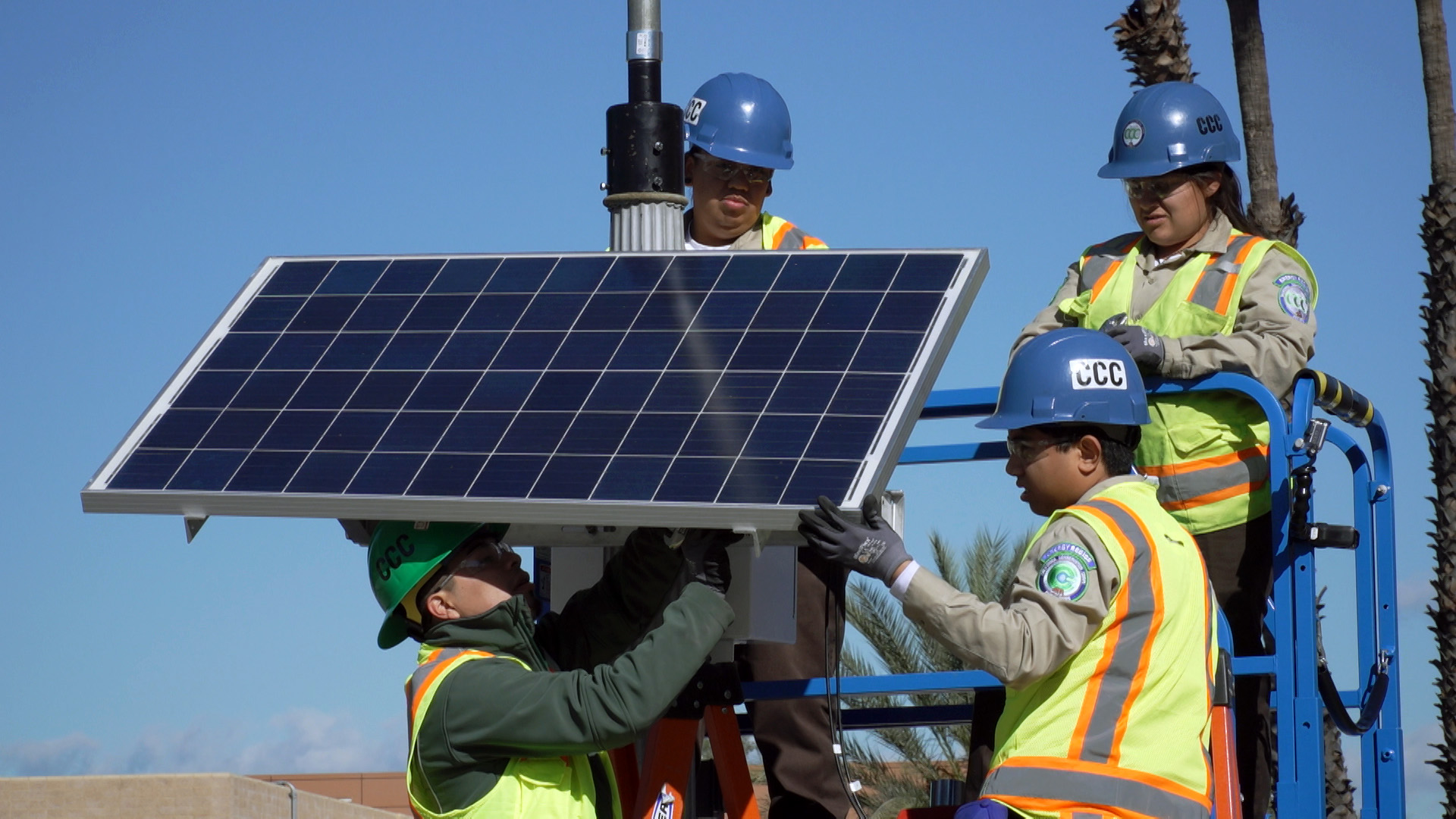Image. Corpsmembers in protective gear afix a solar panel to a street light