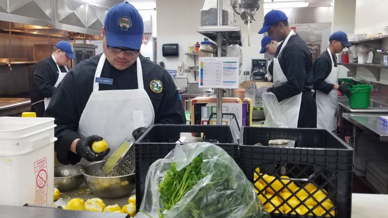 In the foreground, a Corpsmember zests a lemon. Baskets and bags of ingedients are arranged on the shelf around him. In the background, four more Corpsmembers are spread throughout the kitchen, prepping the meal.