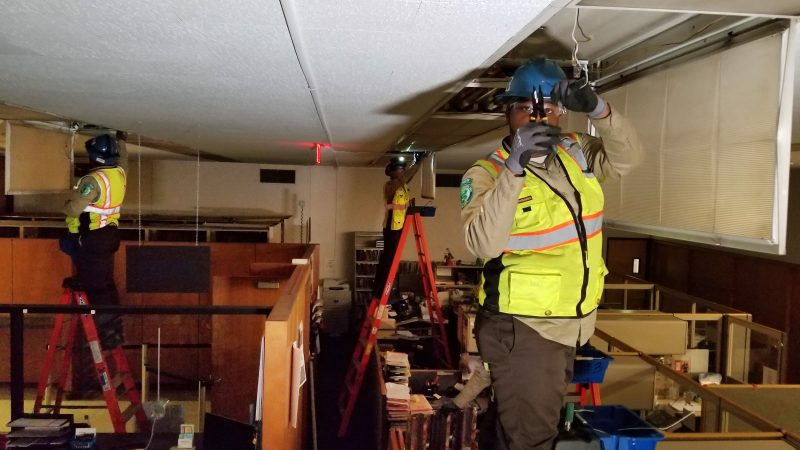 Three Corpsmembers in protective equipment stand atop ladders changing out light fixtures inside a court house clerk's office