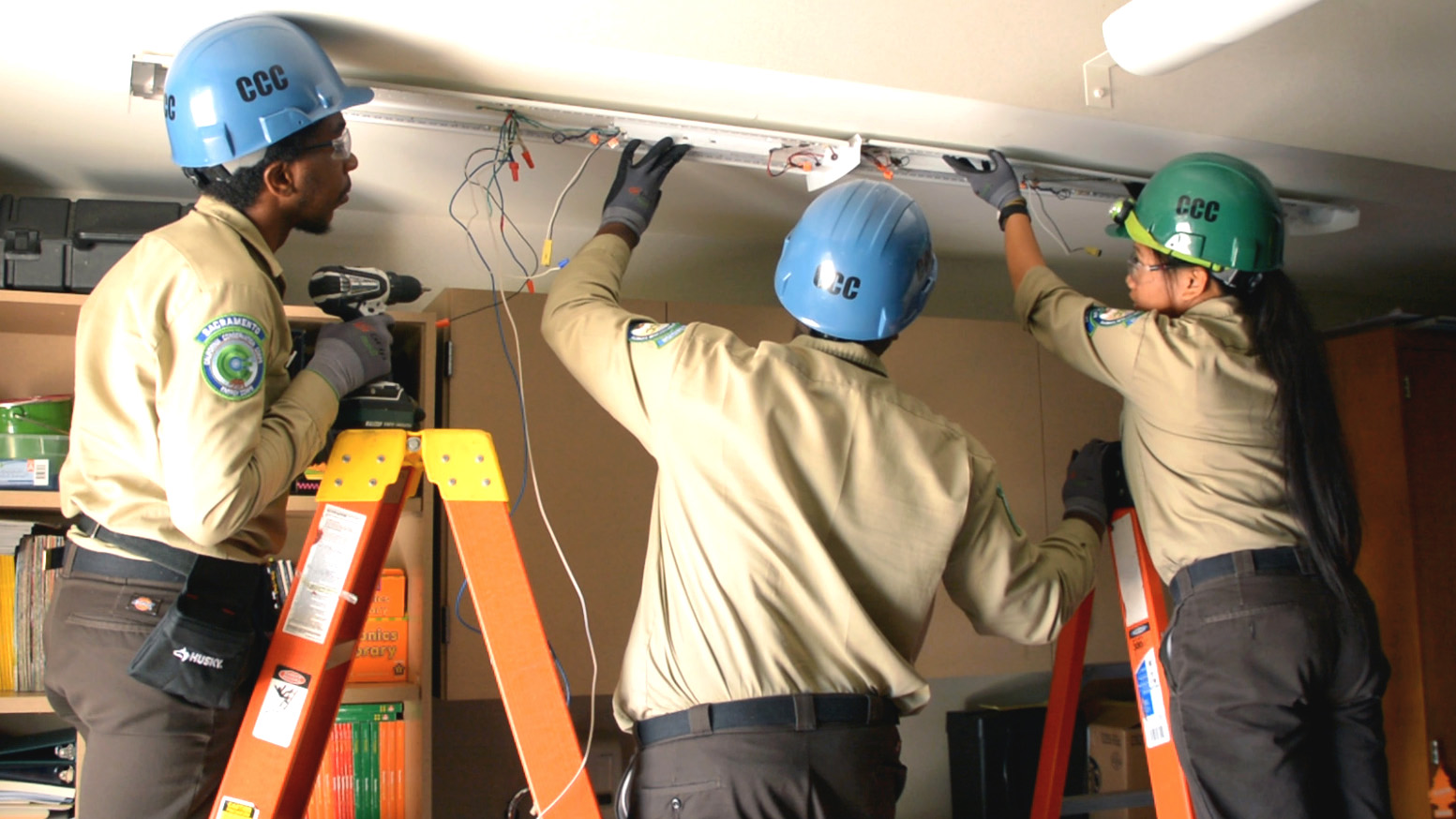 Image. Three Corpsmembers on ladders in protective equipment look at how to install energy efficient light fixture