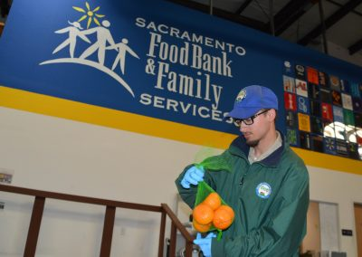 Placer Corpsmember Packages Oranges at Sac Food Bank