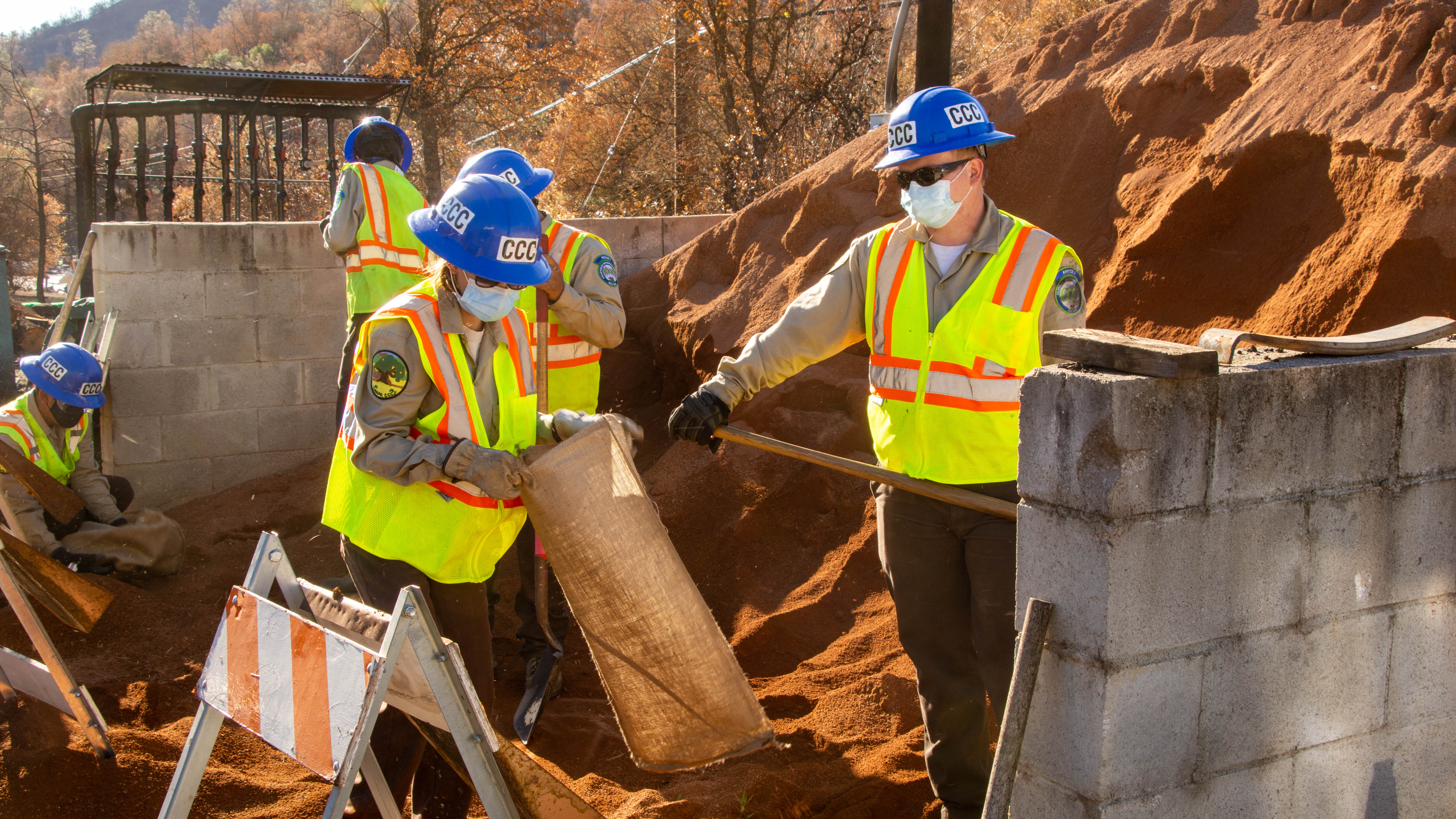Corpsmembes wearing yellow safety jackets and blue helmets use shovels to fill sand bags.
