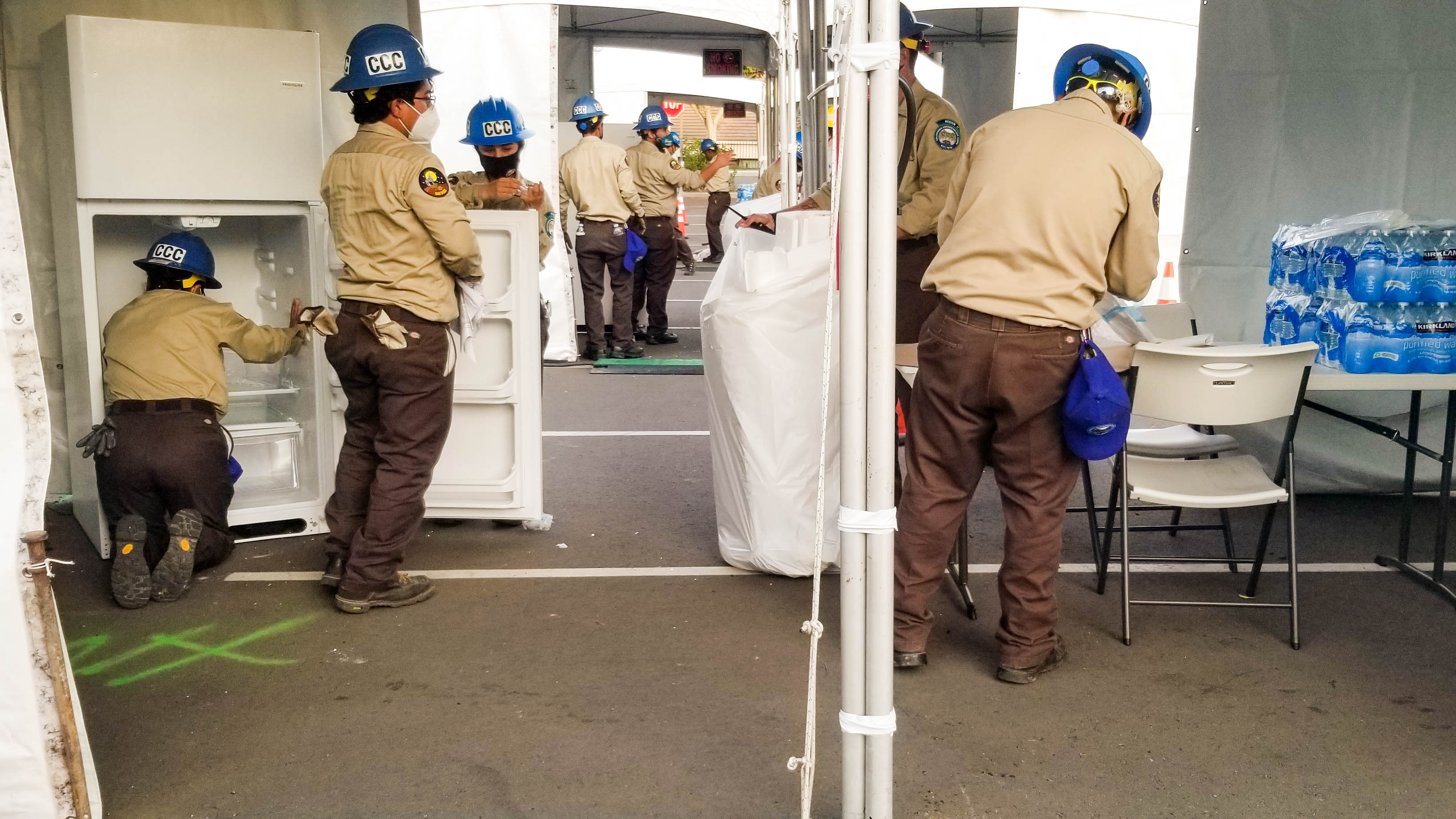 photo, corpsmembers load refrigerators with supplies inside white tents in a parking lot