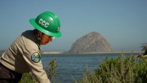 Female Corpsmember with green helmet ans safety glasses extends arm out of frame in foreground, Morro Rock and Morro Bay are in background