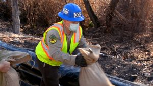 Corpsmember in hard hat and safety vest hands sand bag to another person