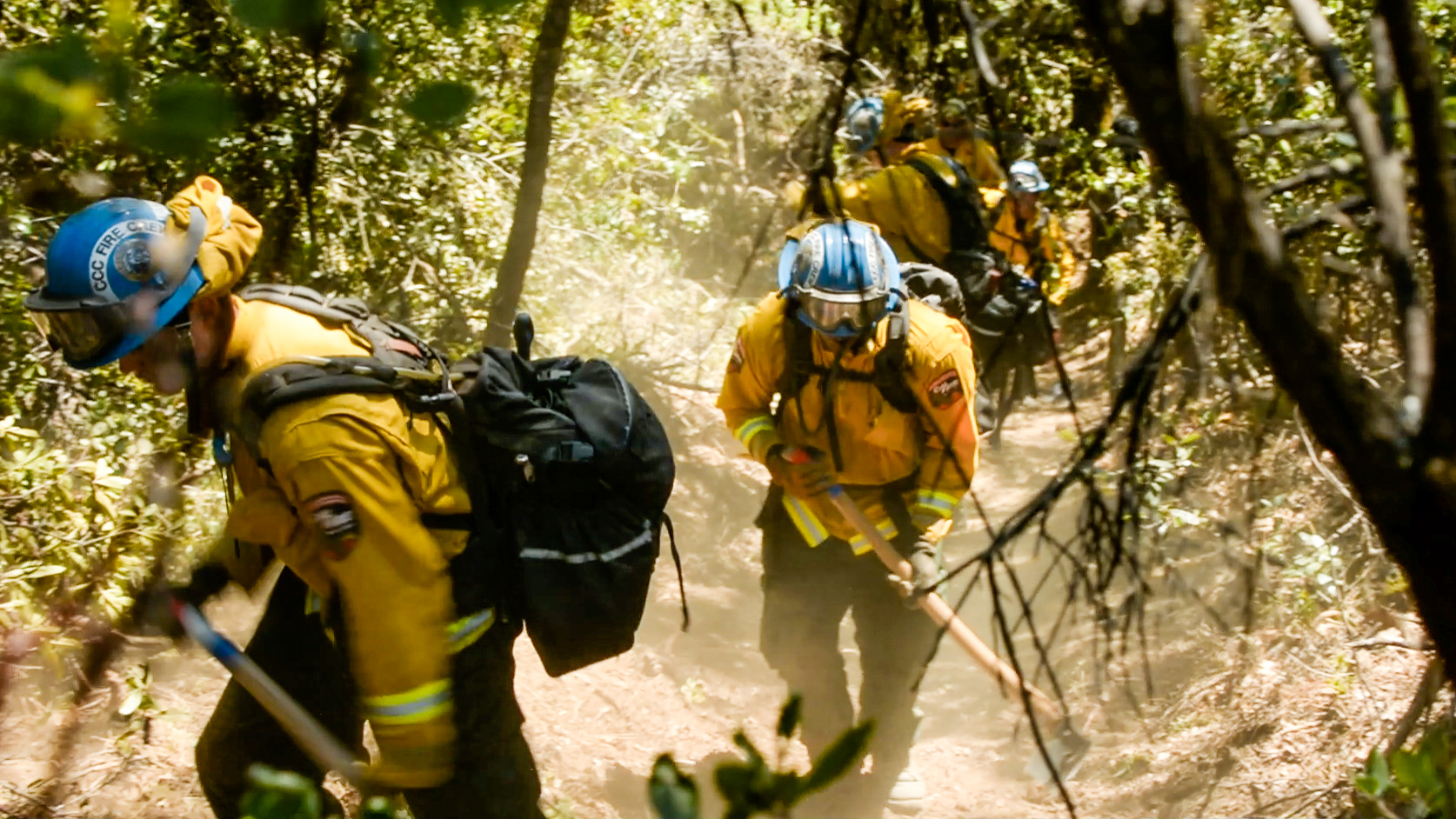 two corpsmembers in fire gear and with hand tools walk through wooded area, with tree limbs and leaves in foreground