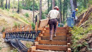 corpsmember carrying wood beam climbs stairs near bridge