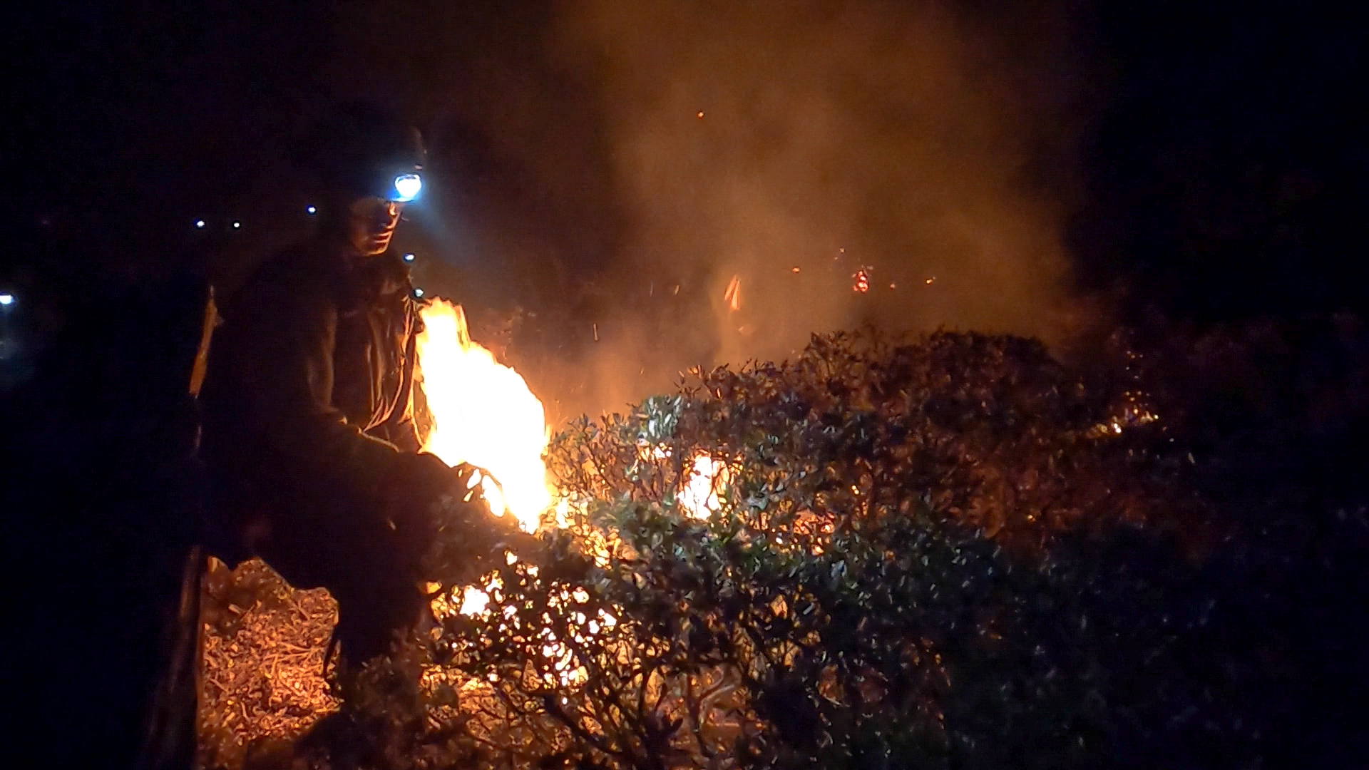 firefighter with head light illuminated by flames uses chainsaw