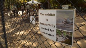 sign reading the habitat is closed for renovations with corpsmembers working in the background
